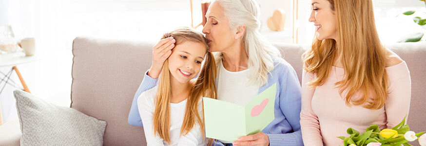 Grandmother kissing granddaughter on the head after reading card