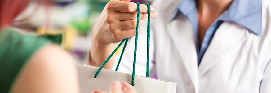 Pharmacist handing a customer a bag